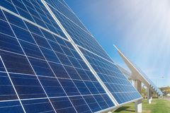 Solar panels or photovoltaic plant in front of a factory building. At a sunny day with visible sun rays royalty free stock image