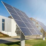 Solar panels or photovoltaic plant in front of a factory building. At a sunny day stock image