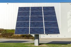 Solar panels or photovoltaic plant in front of a factory building. At a sunny day royalty free stock image