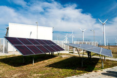 Solar panels in power station against wind turbines background Royalty Free Stock Photos