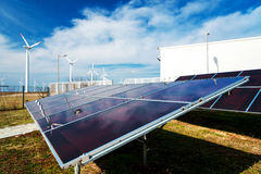 Solar panels in power station against wind turbines background stock photos