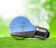Solar panels with pylons in light bulb. Stock Photo