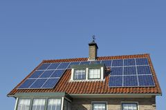 Solar Panels at red roof. Of old house. Copy space in clear blue sky Royalty Free Stock Photography