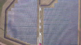 Solar panels and renewable energy farm. Aerial drone video footage looking down onto rows of solar panels in a renewable. Energy farm in the English countryside stock footage