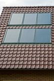 Solar panels on the roof of a building with brown tiles Stock Photos