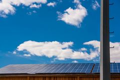 Solar panels on roof. Building with solar panels and sky with white clouds Stock Images