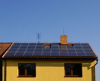 Solar panels on the roof. House with solar panels on the roof and blue sky on background Stock Photos