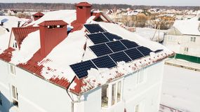 Solar panels on the roof of the house after a heavy snowfall in the winter Royalty Free Stock Photos