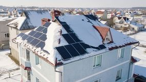 Solar panels on the roof of the house after a heavy snowfall in the winter Royalty Free Stock Images