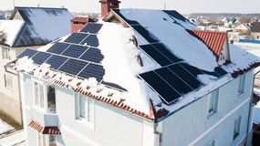 Solar panels on the roof of the house after a heavy snowfall in the winter Stock Images