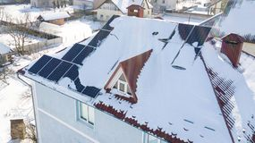 Solar panels on the roof of the house after a heavy snowfall in the winter Stock Photography