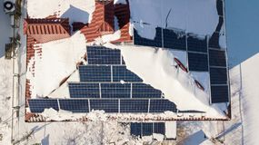 Solar panels on the roof of the house after a heavy snowfall in the winter. Renewable energy production modules Royalty Free Stock Photos