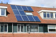Solar panels on the roof of the house in spring. Blue sky with clouds, an open window and solar panels on the roof of the house in the residential area in the Stock Images