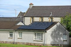 Solar panels on the roof of the house in the summer. Blue sky with clouds and solar panels on the roof of the house in the residential area in the village Royalty Free Stock Photos