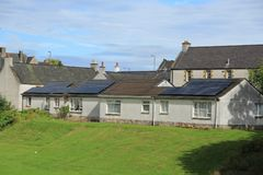 Solar panels on the roof of the houses in the summer. Blue sky with clouds and solar panels on the roof of the houses in the residential area in the village Royalty Free Stock Photo