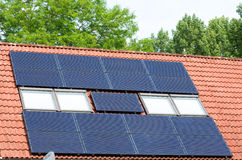 Solar panels on roof. Solar panels mounted on a red roof for collecting energy Royalty Free Stock Image