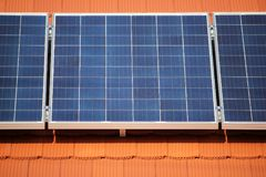 Solar panels on the roof. Solar panels on the red roof of a private house producing electricity, industrial background Royalty Free Stock Image