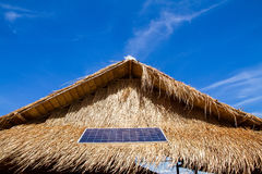 Solar panels on the roof thatched with dry leaf.Global ecology.C Stock Photo