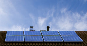 Solar panels on roof top with blue sky in background. Stock Photos