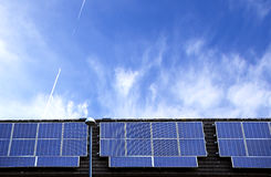 Solar panels on roof top with blue sky in background. Royalty Free Stock Images
