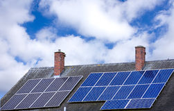 Solar panels on roof top with blue sky in background. Stock Image