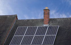 Solar panels on roof top with blue sky in background. Royalty Free Stock Photography