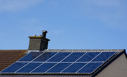 Solar panels on roof top with blue sky in background. Royalty Free Stock Photo