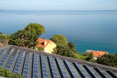 Solar panels and sea in Bergeggi, Italian Riviera. Solar panels in a village of the Italian Riviera. In the background the sea and bottom solar cells Royalty Free Stock Images