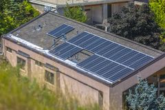 Solar panels sitting on rooftop on sunny day royalty free stock image