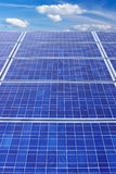Solar panels and sky vertical. Panels of solar collection cells fade towards a bright blue sky with white clouds vertical Royalty Free Stock Images
