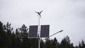 Solar panels and a small wind turbine for the production of environmentally friendly energy stock video footage