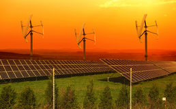 Solar panels with small wind turbines in the sunset Stock Photo
