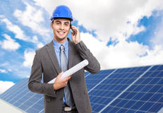 Solar panels. Smiling engineer in front of solar panels Royalty Free Stock Images