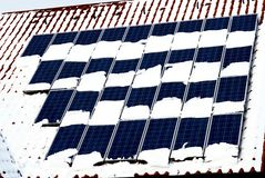 Solar Panels with Snow. Solar panels mounted on the roof a house and partly covered by snow Stock Images