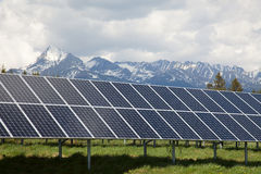 Solar panels with snowy mountains in the background Stock Photography
