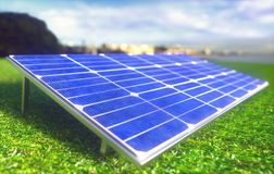 Solar Panel Ecological Renewable Energy. Solar panels spread across the field on the green grass. In the background the city for which energy is provided stock image