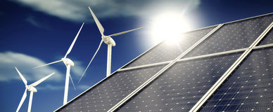 Solar panels or sun collectors and wind turbines in front of blue sky Stock Photos