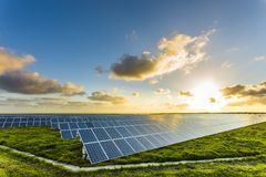 Solar panels at sunrise with cloudy sky in Normandy, France. Solar energy, modern electric power production technology. Renewable energy concept Stock Photography