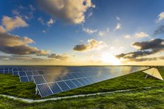 Solar panels at sunrise with cloudy sky in Normandy, France. Solar energy, modern electric power production technology. Renewable energy concept Stock Image