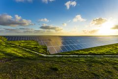Solar panels at sunrise with dramatic cloudy sky in Normandy, France. Modern electric power production technology. Environmentally friendly electricity Stock Photos
