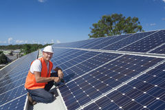 Solar panels with technician. Young technician installing solar panels on factory roof Stock Photo