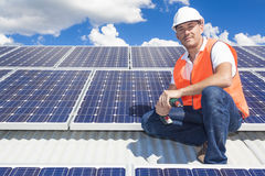 Solar panels with technician. Young technician installing solar panels on factory roof Stock Photos