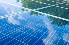 Solar panels with tree reflection. Green trees and blue sky reflection on solar panels. Go green with renewable energy stock photo