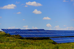 Solar panels under a blue sky. Ground solar panels in a field under a blue sky Stock Image