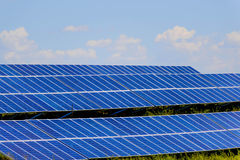 Solar panels under a blue sky. Ground solar panels in a field under a blue sky Stock Photography