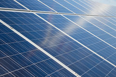Solar panels with vague reflection of wind turbine Royalty Free Stock Photography