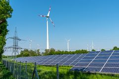 Solar panels, wind engines and an electricity pylon. Seen in Germany Royalty Free Stock Images