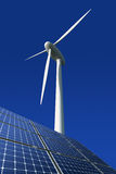 Solar panels and wind turbine against blue Royalty Free Stock Image