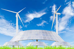 Solar panels and wind turbine on green grass field against blue Stock Photos
