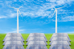 Solar panels and wind turbine on green grass field against blue Stock Photography